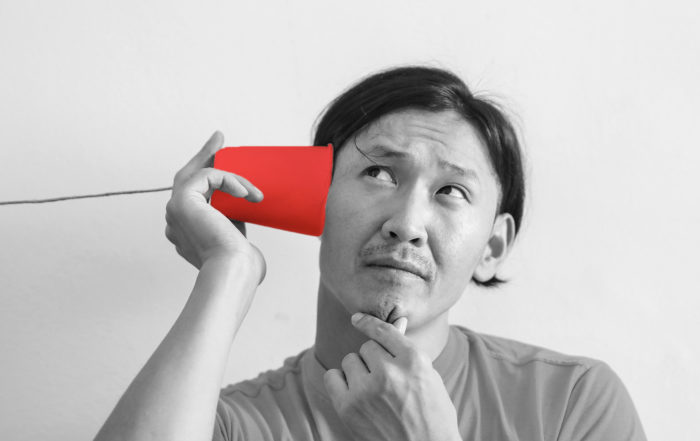 man listening to a plastic cup telephone